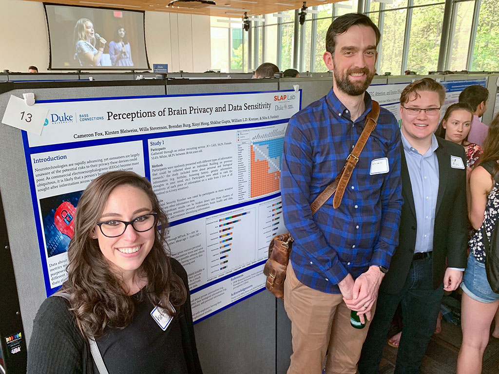 Dr. William Krenzer and two lab particpants posing in front of their poster during the 2018 Bass Connections Poster Session