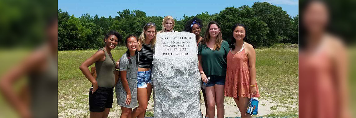 A group of Huang Fellows poses in front of a Wright Brothers memorial